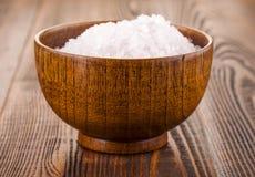 在一木杯的白色腌制槽用食盐木表面上 库存图片