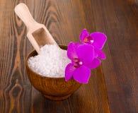 在一木杯whith Orhid的白色腌制槽用食盐木表面上 库存照片