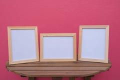 在一木的三张照片框架在桃红色背景 免版税库存照片