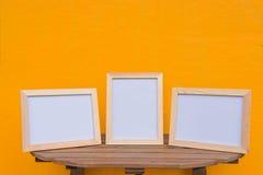 在一木的三张照片框架在黄色背景 库存照片