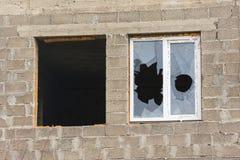 在一未完成家一个的两个窗口没有框架和玻璃,另一块残破的玻璃 库存照片