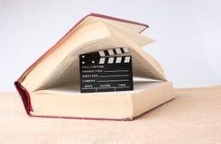 在一本书旁边的电影拍板在帆布 免版税图库摄影