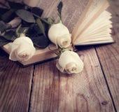 在一本书的白玫瑰在葡萄酒样式。 免版税库存图片