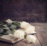 在一本书的白玫瑰在葡萄酒样式。 库存图片
