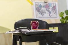 在一本书的红色苹果在学校 库存照片