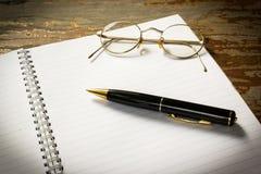 在一本开放书的一支黑笔与玻璃 库存照片