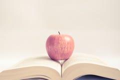 在一本开放书的红色苹果在葡萄酒口气 免版税库存照片