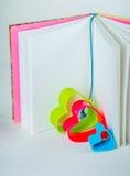 在一本开放书里面的蓝色红色和绿色心脏与书签 库存照片