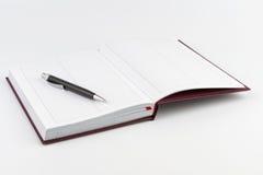 在一本开放日志的黑色圆珠笔 免版税库存图片
