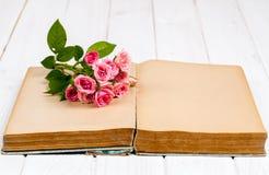 在一本旧书的玫瑰在白色木背景 花 库存照片
