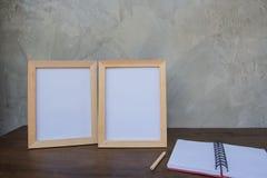 在一本木桌和书上的两张照片框架在灰色墙壁背景 库存图片