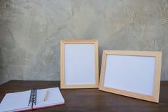 在一本木桌和书上的两张照片框架在灰色墙壁背景 库存照片
