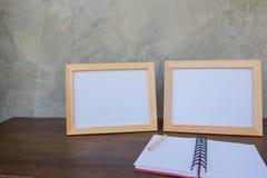 在一本木桌和书上的两张照片框架在灰色墙壁背景 免版税库存图片