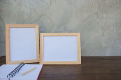 在一本木桌和书上的两张照片框架在灰色墙壁背景 免版税图库摄影