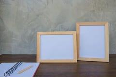 在一本木桌和书上的两张照片框架在灰色墙壁背景 免版税库存照片