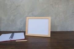 在一本木桌和书上的照片框架在灰色墙壁背景 库存照片