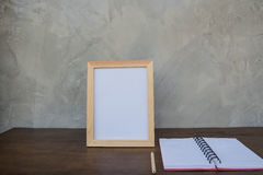 在一本木桌和书上的照片框架在灰色墙壁背景 免版税库存照片