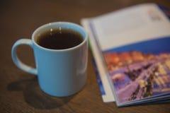 在一本木桌和旅行杂志的白色茶杯 免版税库存照片
