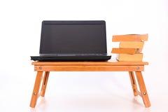 在一本木桌&旧书上的膝上型计算机 免版税库存图片