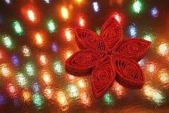 在一本欢乐诗歌选前面的红色闪烁雪花圣诞节装饰品点燃背景 图库摄影