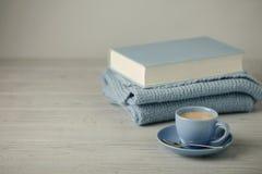 在一本浅兰的杯子和书的咖啡在与knitt的蓝色捆绑 免版税库存照片