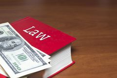 在一本红色书的很多美元 在书有法律的题字 免版税库存照片