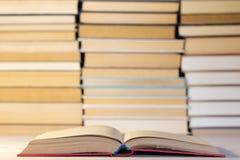 在一本蓝色精装书的一本开放书反对在堆堆积的许多书背景  图库摄影