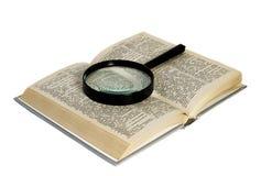 在一本被打开的书的放大玻璃 在一个空白背景 免版税库存照片