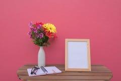 在一朵木桌上的照片框架和书和花在瓶子在桃红色背景 库存照片