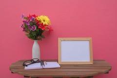 在一朵木桌上的照片框架和书和花在瓶子在桃红色背景 免版税库存图片