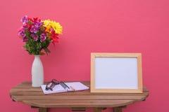 在一朵木桌上的照片框架和书和花在瓶子在桃红色背景 免版税库存照片