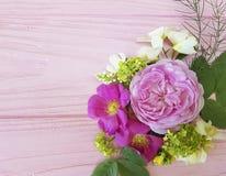 在一朵桃红色木背景茉莉花的玫瑰美好的花束框架,木兰 免版税库存图片