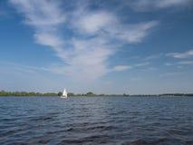 在一朵湖和白色云彩的白色小船航行在天空 免版税库存照片