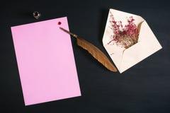 在一朵白纸板料和花的翎毛钢笔 免版税库存图片