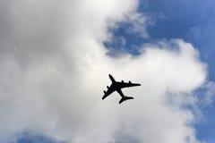 在一朵白色云彩下的飞机飞行 免版税库存照片