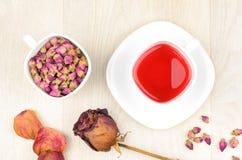 在一朵白色杯子、热的茶和干玫瑰色花的香水月季 库存照片