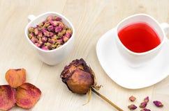 在一朵白色杯子、热的茶和干玫瑰色花的香水月季 免版税图库摄影