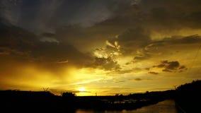 在一朵移动的云彩后的时间间隔日落 给在沼泽上的美好的金黄光 股票录像