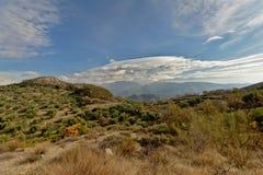 在一朵蓝天一大灰色云彩下的谢尔内华达山 免版税库存照片