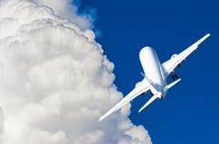 在一朵蓝天和美丽如画的云彩的一架飞行飞机 免版税图库摄影