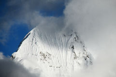 在一朵黑暗的云彩的积雪的高山 免版税库存图片