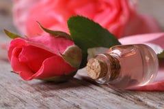 在一朵玻璃瓶和桃红色花的玫瑰油在木桌上 库存图片