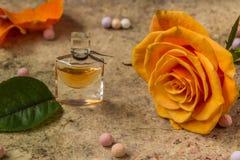 在一朵玻璃瓶和桔子玫瑰色花的香水 免版税库存图片