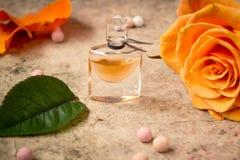 在一朵玻璃瓶和桔子玫瑰色花的香水 免版税图库摄影