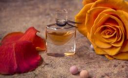 在一朵玻璃瓶和桔子玫瑰色花的香水 库存图片