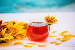 在一朵玻璃透明杯子和黄色花的茶 免版税图库摄影
