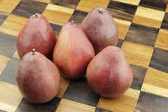 在一杆木棋枰的五个红色梨 免版税库存图片