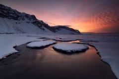 在一条下雪的河的日出 免版税库存图片