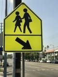 在一条主要公路旁边的明亮的黄色步行行人穿越道标志 库存照片