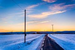 在一条乡下公路的日落通过在农村的积雪的领域 免版税库存照片
